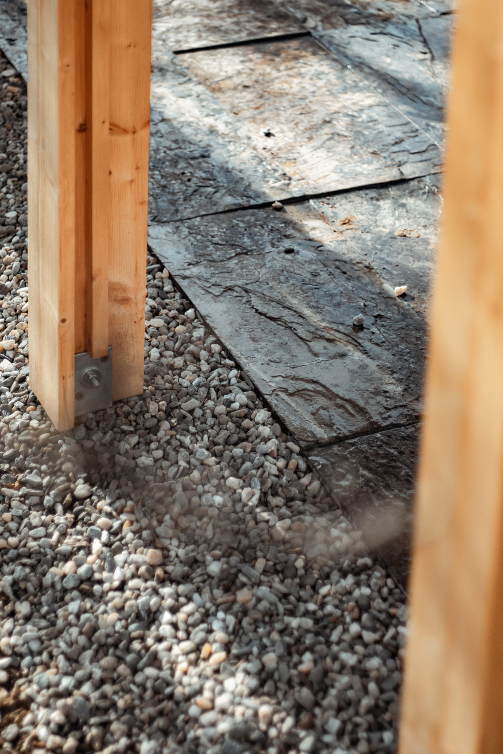 T section wood pillars held by metal post bases right over gravel area. Next to the grey gravel the pavement is made of rough and varnished slate stone tiles.