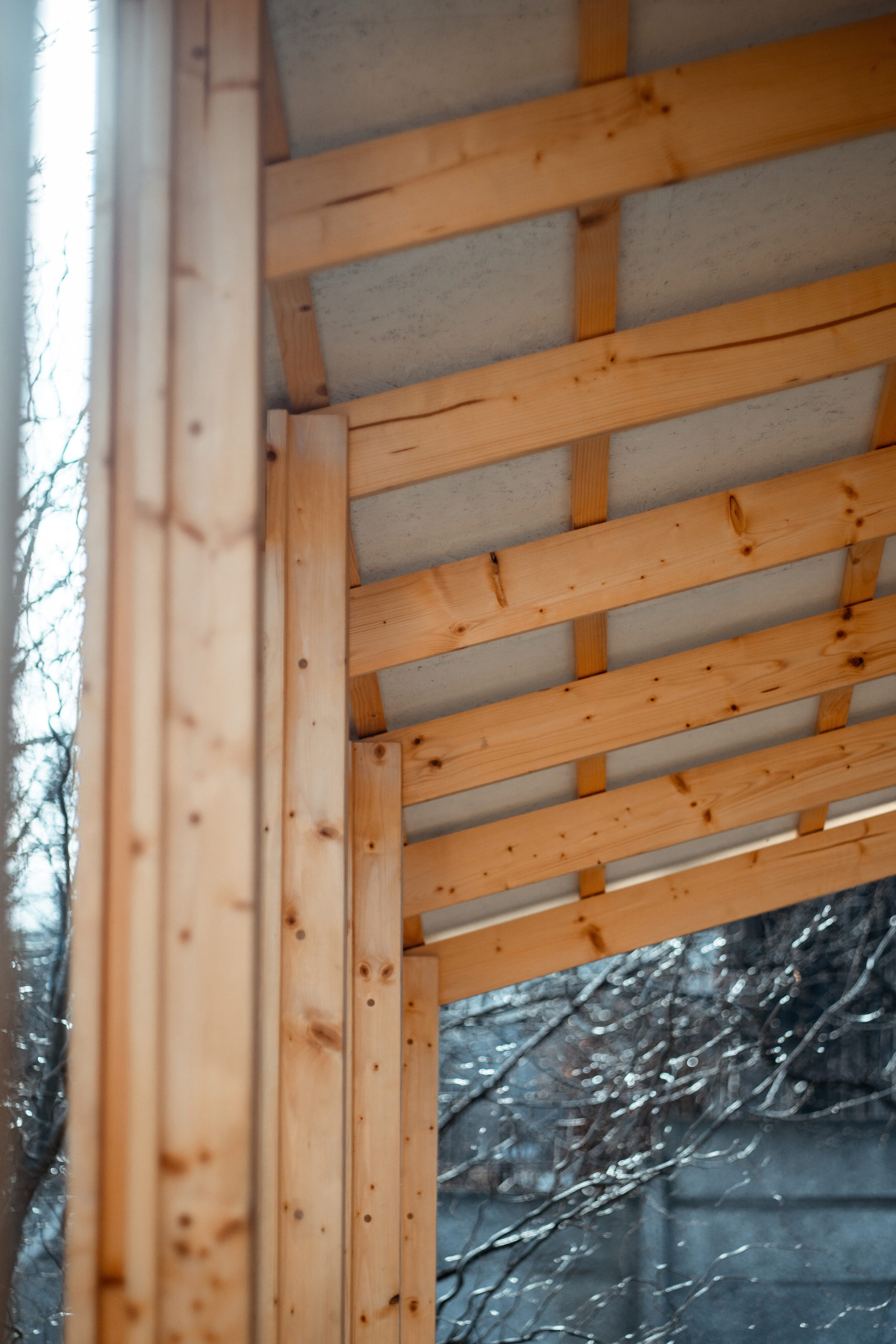Rafters made out of evergreen wood planks are inserted into the wooden pillars.