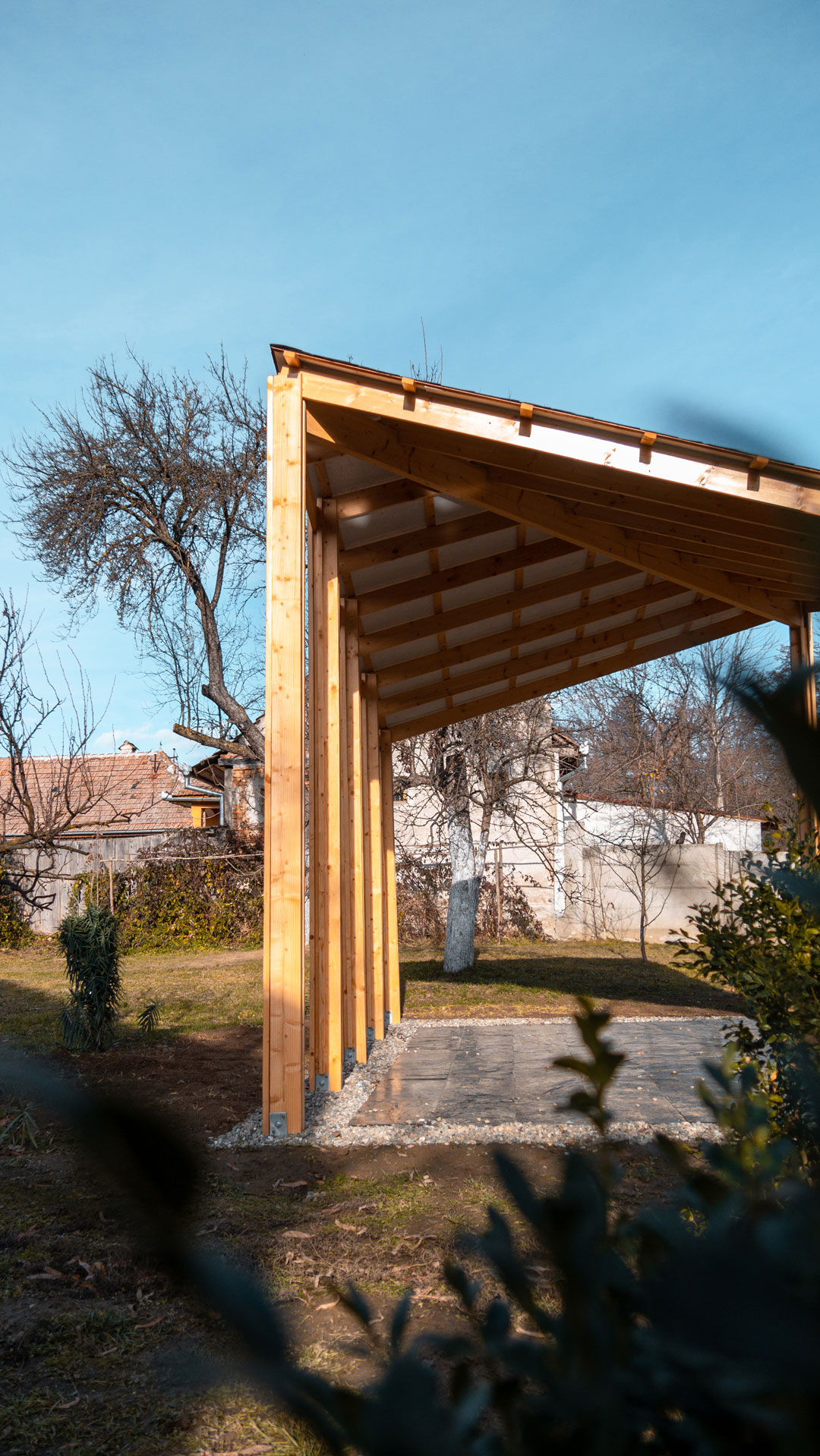 Open evergreen wood built pavilion, with gravel and varnished slate stone pavement.