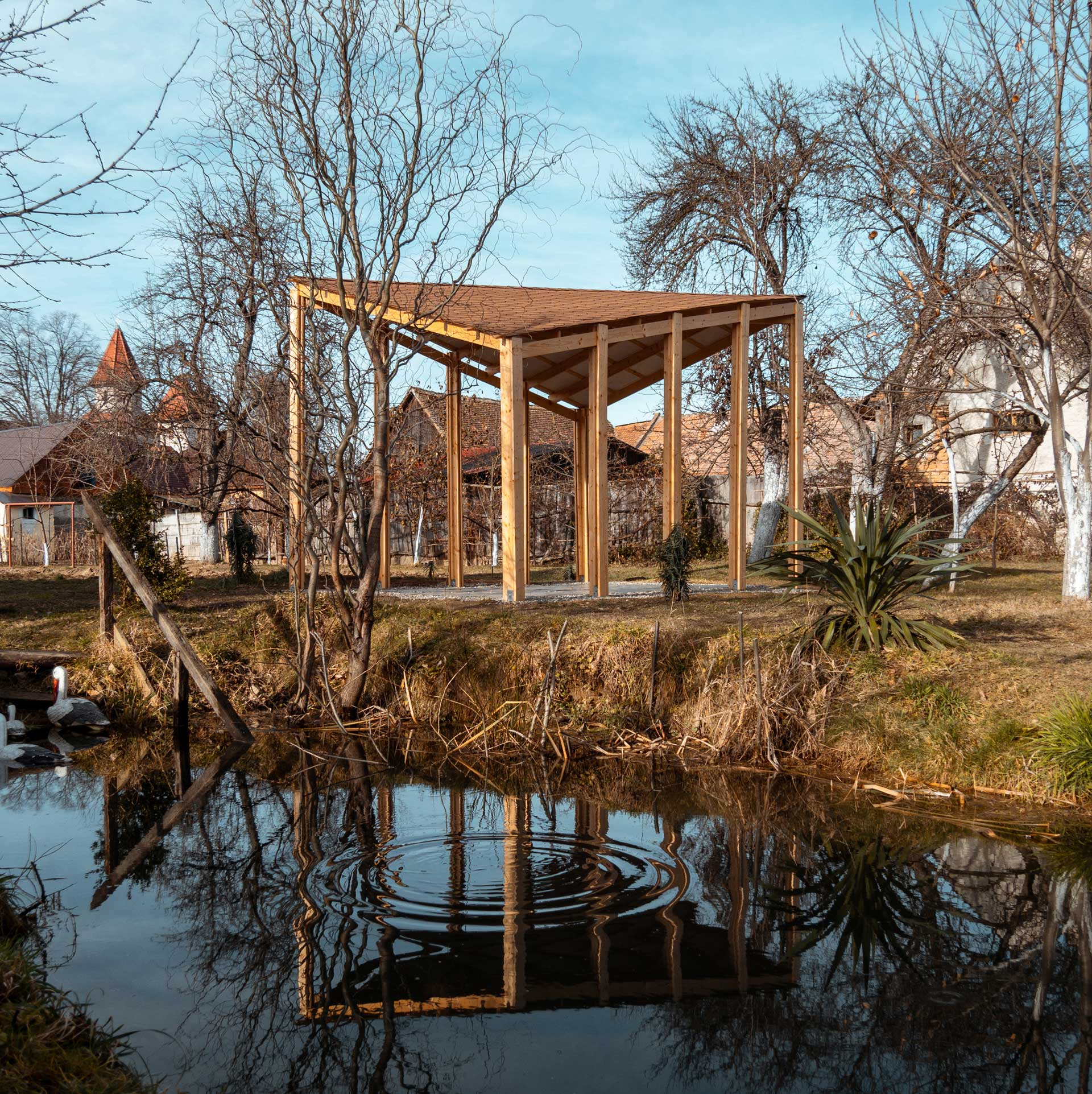 The wood pavilion reflected in our small pond in the backyard. In the background the village's church is visible through the trees..