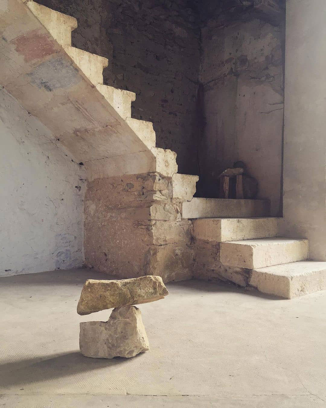 Hard, rough limestone staircase attached to a 90 degree wall with a rough stone sculpture in the foreground and another rough stone sculpture in the background on the stairs